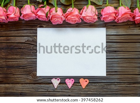 Single horizontal sheet of blank white paper in between three little Valentines Day paper heart objects and neatly arranged row of pink roses - stock photo