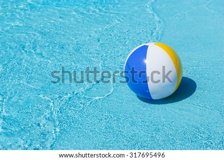Single Inflatable Striped Beach Ball Floating in Shallows of Water at Shore of Wave Pool with Copy Space - stock photo
