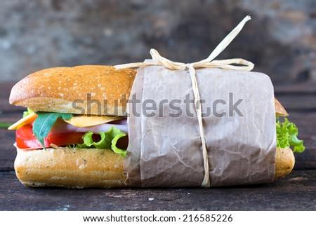 Single Italian panini sandwich on the wooden background,selective focus - stock photo