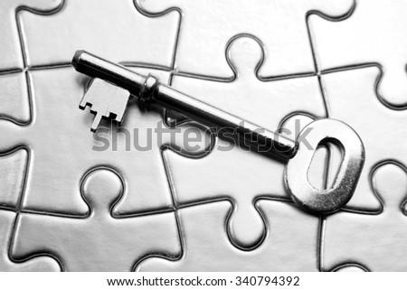 Single key on jigsaw puzzle - stock photo