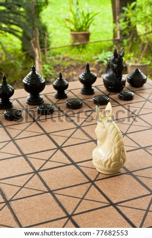 Single knight looking forward the chess board at the opposing pieces. A clipping path is included for easy extraction. - stock photo