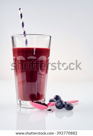Single large glass of fresh blueberry and exotic acai berry blended beverage with one straw next to a pink spoon against a white background - stock photo