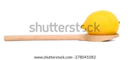 single lemon on wooden spoon isolated on white  - stock photo
