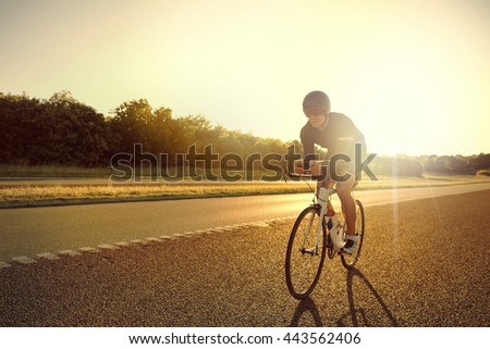 Single male bicyclist wearing shorts, helmet and sunglasses training for long distance racing on road bike at sunrise with copy space in front - stock photo