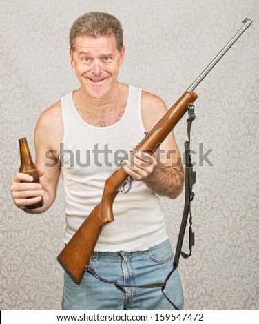 Single male hillbilly holding beer and rifle - stock photo