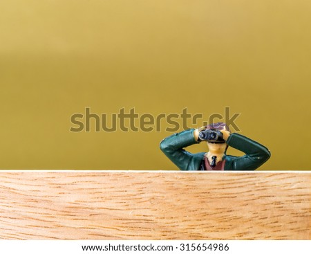 Single male model looking through binoculars secretly spies on an unknown person or event with copy space room - stock photo