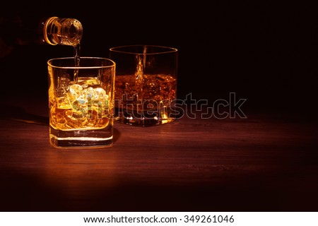 Single Malt Whiskey in a glass on a wooden table top. - stock photo