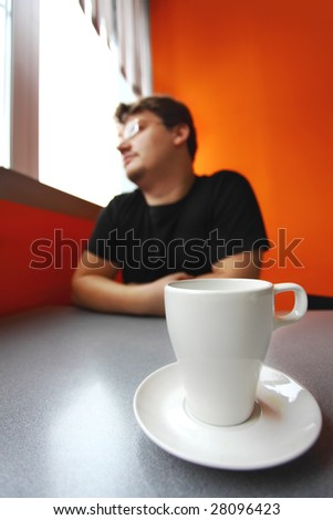 single man looks to window and coffee cup stand on the table