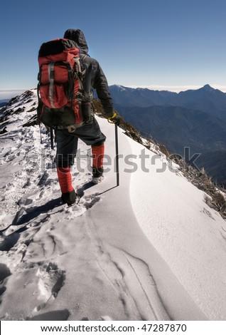 Single man of climber walk alone on top of snow ice winter mountain. - stock photo