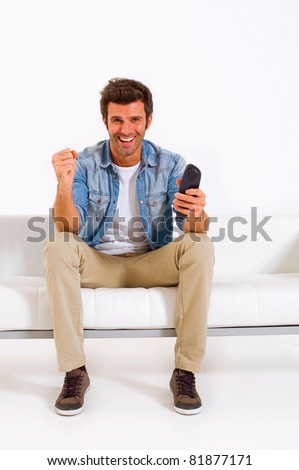 single man on the couch watching TV - stock photo