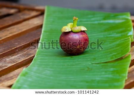 Single mangostin sitting on fresh green banana leaf on wooden table - stock photo