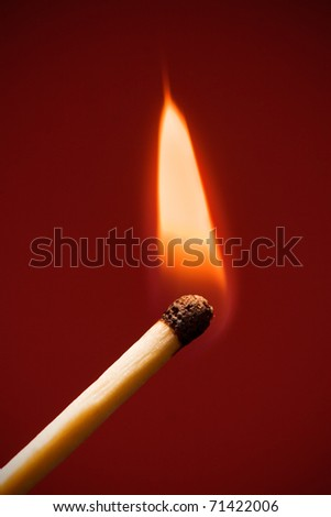 single matchstick flaming on dark red background. vertical composition.