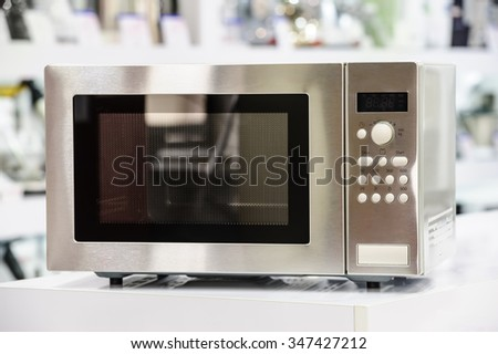 single microwave oven at retail store shelf, defocused background - stock photo