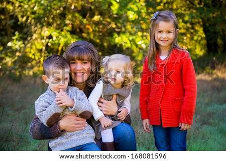 Single mom outdoors with three children in her arms including two girls and a boy. - stock photo