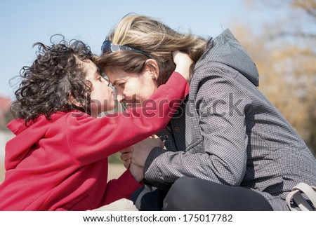 Single mother and her son having a devotional outdoors. Praying for the city - stock photo