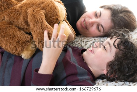 Single mother and son laying in bed at home. - stock photo