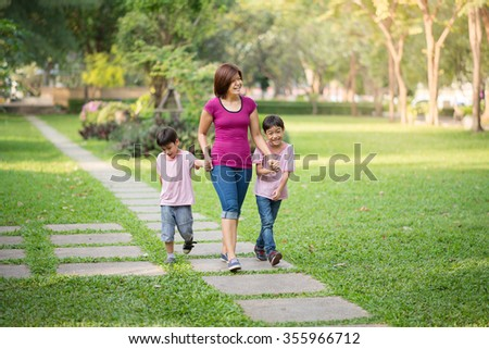 single mother walking in the park with sons - stock photo