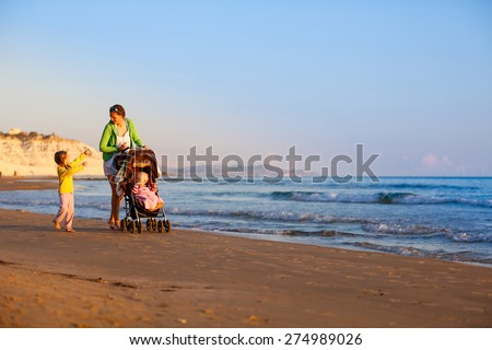 Single mother walking with her daughter and son, talking and pushing a stroller on a sandy beach in late summer, enjoying the evening chill. Family vacation, traveling with children concept.  - stock photo