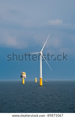 Single Offshore Wind Turbine and a Substation (Transformer) in a Windfarm under construction  off the English Coast - stock photo