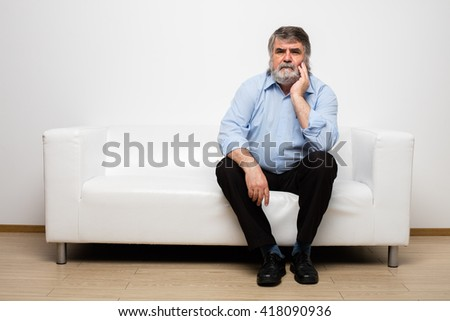 single old men sitting on white couch - stock photo