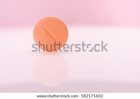 Single orange pill on white surface  - stock photo