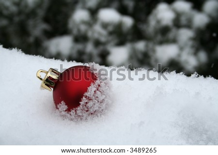 Single ornament on the ground in the snow - stock photo