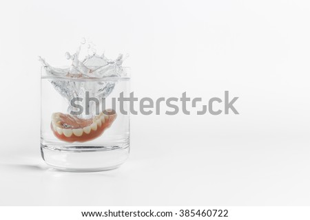 Single orthodontic dentures mold falling into clear glass of water with splash over white background next to copy space on side - stock photo