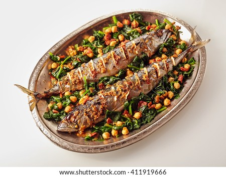 Single oval shaped silver platter full of two whole cooked mackerel fish stuffed with spices and garnished with garbanzo peas and vegetables - stock photo