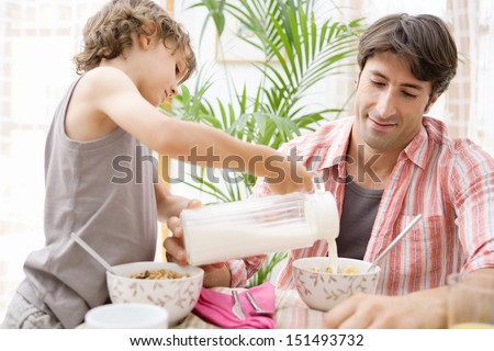 Single parent dad and his young son having breakfast together and eating cereals with the boy helping and pouring milk in his father cereal bowl during a sunny morning at home. - stock photo