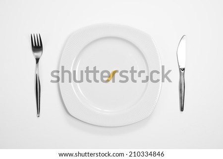 Single pasta on the middle of a plate, knife and fork.