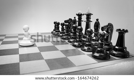 Single pawn against many enemies as a symbol of difficult unequal fight or struggle of minorities. - stock photo