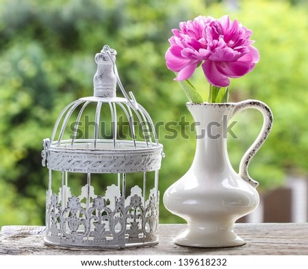 Single pink peony flower in white ceramic vase and vintage decorative cage on rough rustic wooden table in lush spring garden. - stock photo