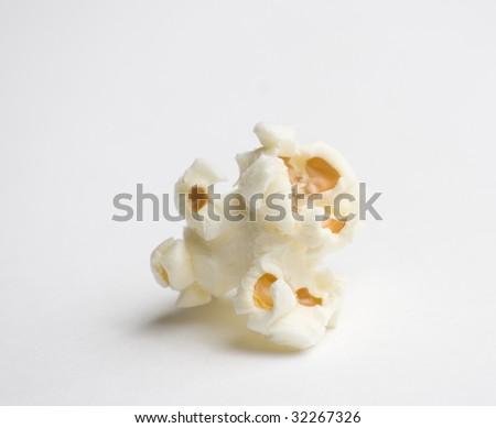 Single popped popcorn on white - stock photo