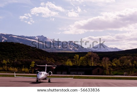 single private jet on tarmac with mountains in background - stock photo
