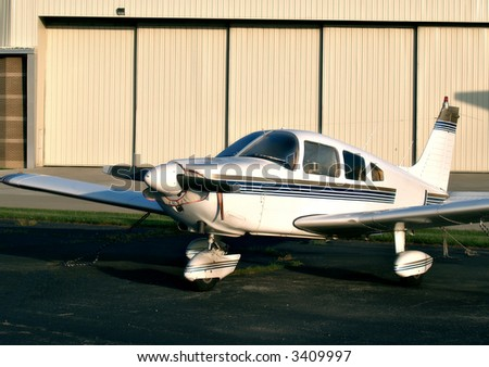 Single prop airplane sits in a tie-down area on the airfield in front of a large hangar - stock photo