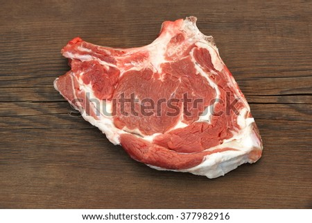 Single Raw Beef Rib Eye Steak On The Brown Wood Cutting Board Or Table Isolated On White Background, Close Up, Top View