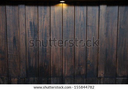 Single ray light on antique wooden wall - stock photo