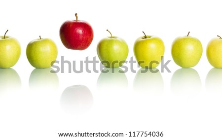 Single red apple floating above a row of green apples isolated on white background. - stock photo