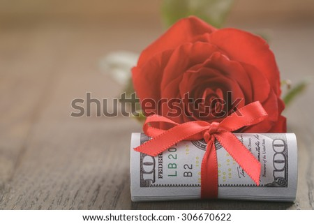 single red roses and bunch of dollar bills, vintage toned - stock photo