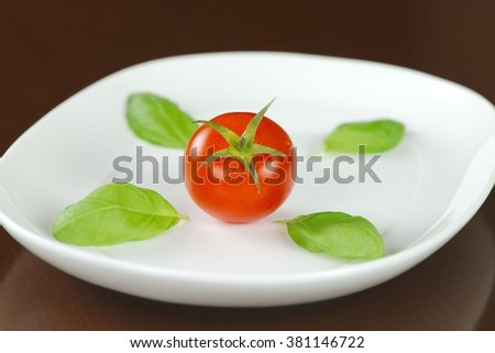 Single red tomato in water drops with basil leaves on white oval plate