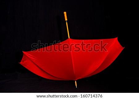 Single red umbrella on black background - stock photo