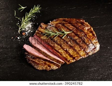 Single roasted medium rare sliced flank beef piece with rosemary over dark table background