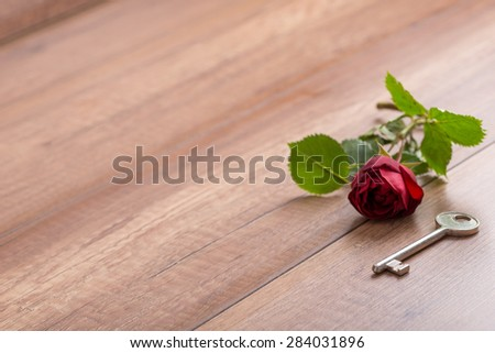 Single Romantic Red Long Stemmed Rose Lying on Wooden Surface with Copy Space Next to Old Fashioned Brass Key. - stock photo