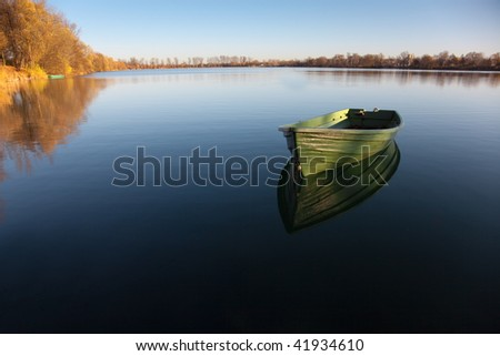 Single Rowboat on Lake with Reflection in the Water - stock photo