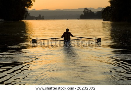 Single rower at sunrise - stock photo