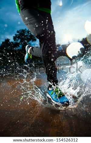 Single runner running in rain and making splash in puddle - stock photo