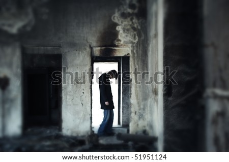 Single sad man standing in the door within the dark trashy interior. Shallow depth of field due to the tilt lens added - stock photo
