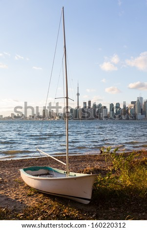 Single sailing boat beached on sandy shore of Lake Ontario on Wade Island of Toronto Islands with skyline of city in the background - stock photo