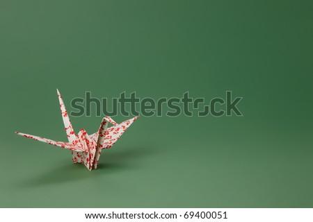 Single Sakura Paper Crane against green background. - stock photo