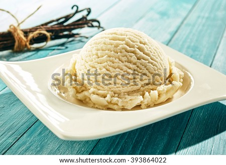 Single scoop of creamy vanilla ice cream on a stylish modern plate on a blue wooden picnic table outdoors in summer with a bundle of dried vanilla pods behind
